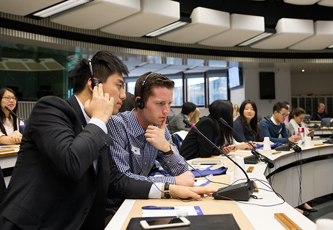 Undergraduate business student Matthew Robinson wears a headset and listens to a translation at the European Commission.