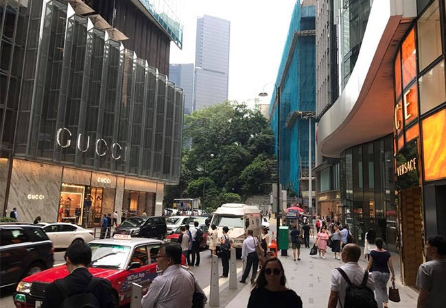 Pedestrians move across a street in Hong Kong in front of a store with several large Gucci signs.