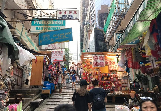 Pedestrians make their way through busy shops and stalls that line a narrow Hong Kong street.