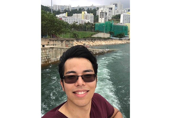 Undergraduate business student Jesse Aguilar takes a selfie during a river cruise while studying abroad in Hong Kong.