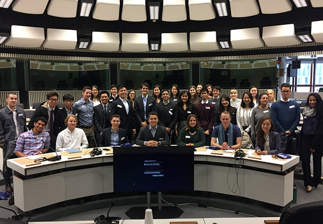 Students gather for a group photo in a large room at the European Parliament in Brussels.