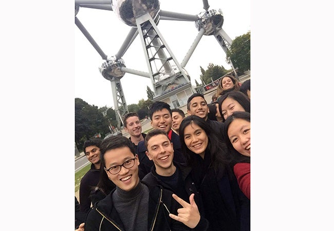 A group of students gather for a photo together in front of a large metal structure in Brussels.