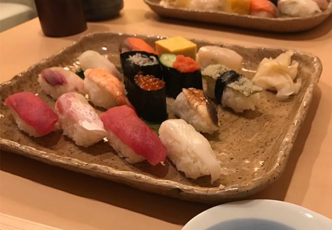 A plate of sushi arranged on a table in a low-light setting in Tokyo.
