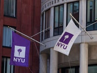 NYU flags outside of the Henry Kaufman Management Center