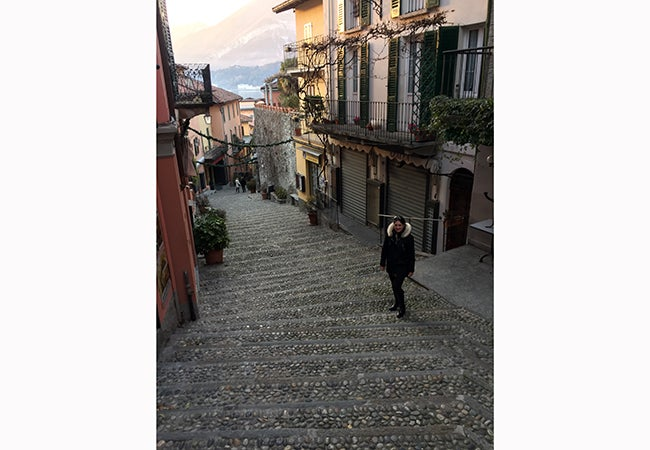 MBA student Natasha Lim stands on a quiet, winding street in the town of Bellagio, Italy.