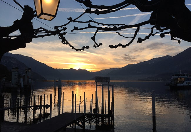 A sunset casts shadows across a dock in the water of Lake Como in Italy.