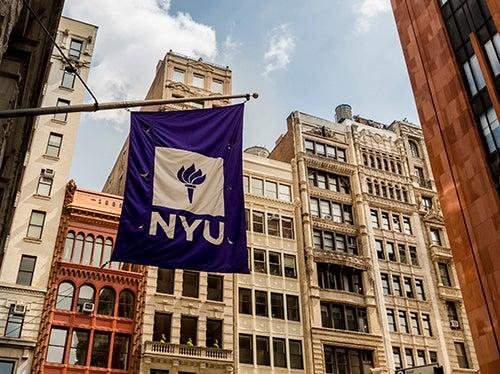 NYU flag against downtown skyline