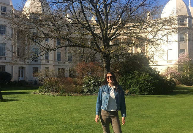 MBA student Alyssa stands in front of a building on a blue-sky day at the London Business School campus.