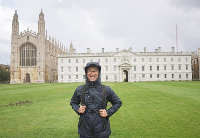 Stern MBA student Dennis Au, wearing rain gear, stands before a building on the campus of the London Business School while studying abroad.