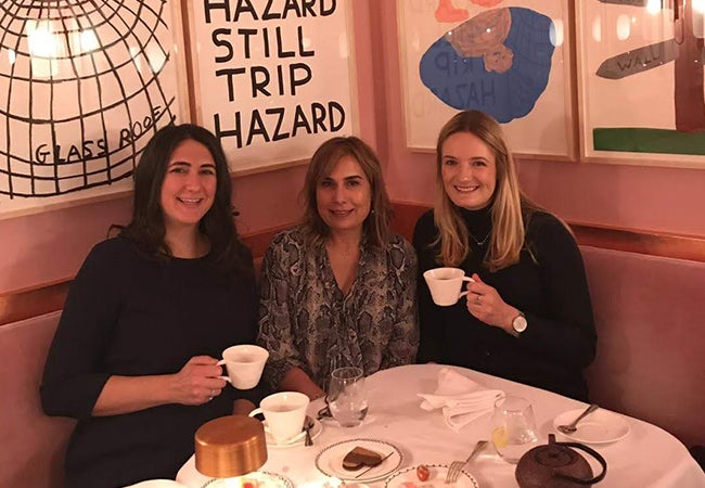 Three women smile and share tea in a corner seat at a cozy cafe.