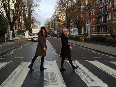 MBA student Alyssa and a friend cross the iconic Abbey Road intersection on a brisk day.