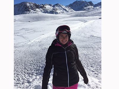 MBA student Ashley Grand, dressed in ski goggles and gear, stands before a snowy mountain region of the Italian Alps.