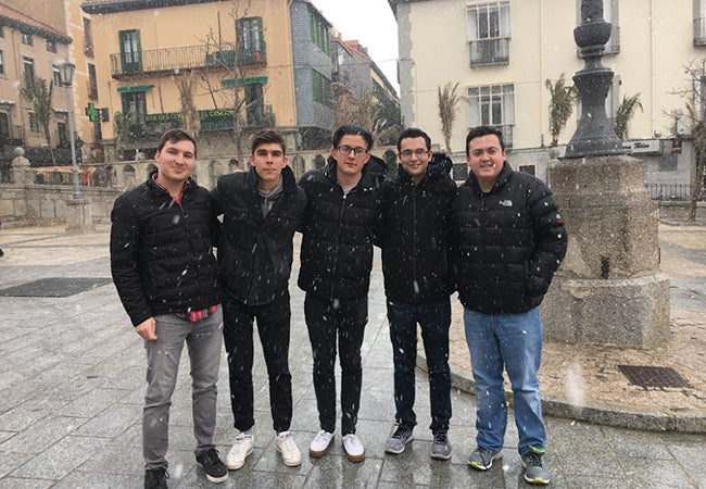Business student Kristian poses with new friends outside in freezing rain while studying abroad in Spain.