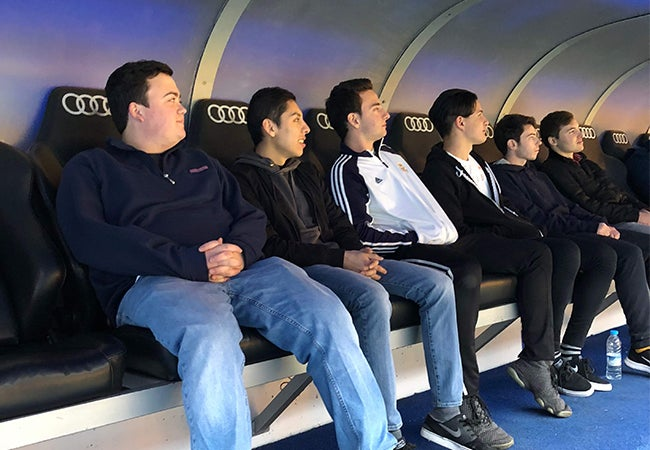 A group of students sit in jet black stadium seats during a facility tour while studying abroad in Spain.