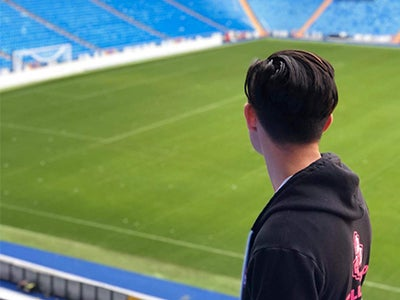 Business student Kristian looks out over an empty soccer stadium far below him.