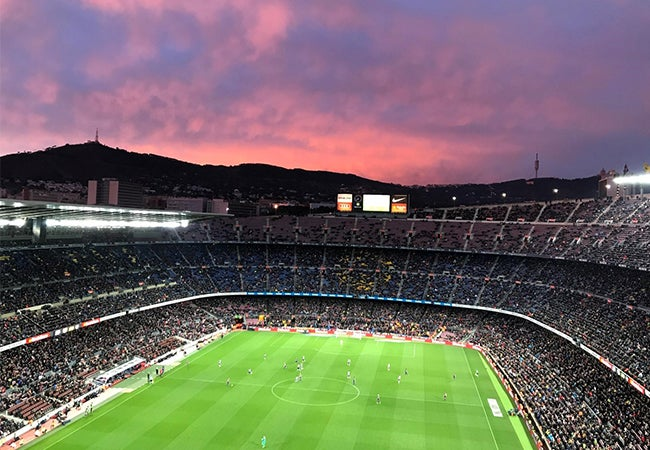 Football teams FC Barcelona and Levante UD compete in a stadium in Barcelona, Spain during sunset.