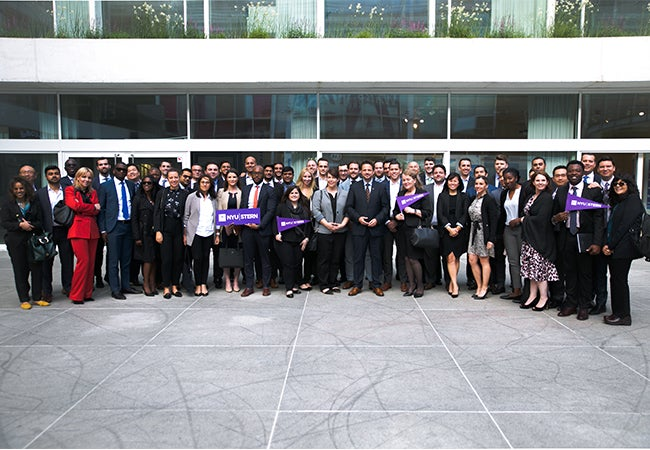 Executive MBA students pose outside of a classroom building with Stern signs and memorabilia.