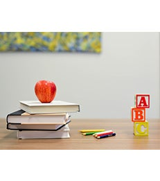 Desk with apple, books, colored pencils and blocks