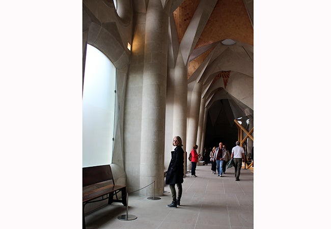 Undergraduate student Michelle Enkerlin looks back while walking through a cavernous building.