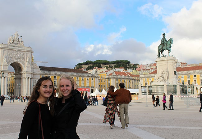 Undergraduate student Michelle Enkerlin stands with a friend near a statue of a man on a horse in a city square.