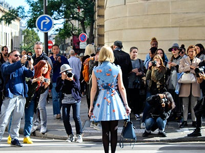 Undergraduate student Michelle Enkerlin wears a blue dress in front of photographers on a city street.