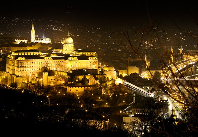 An aerial view of Budapest shows several large stone buildings and complexes lit up a night.