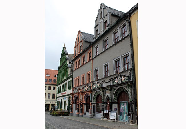 A row of gray and white buildings with colorful accents stands on a stone street in Germany.