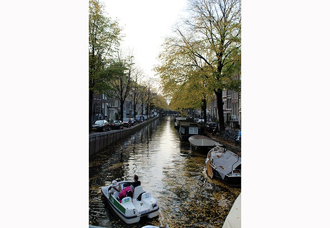 Three passengers begin to steer a paddle boat down a canal in Amsterdam covered in leaves from nearby trees.