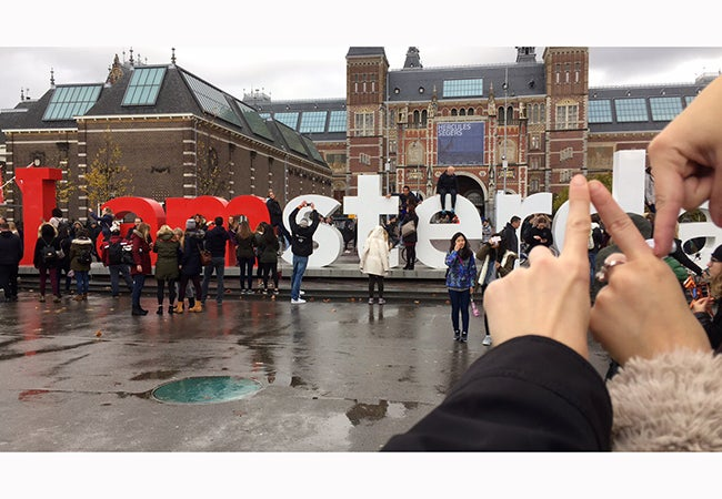 "Three hands form the letter ""N"" to replace a portion of a sign that reads ""I amsterdam"" so the sign spells ""I am Stern."""
