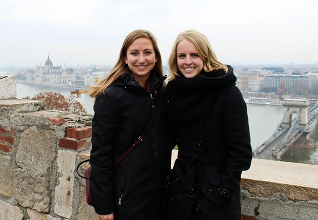 Undergraduate business student Michelle Enkerlin stands before a river in Budapest with a friend while studying abroad in Europe.