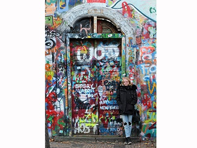 Undergraduate business student Michelle Enkerlin stands in front of a door covered in colorful graffiti while studying abroad in Germany.