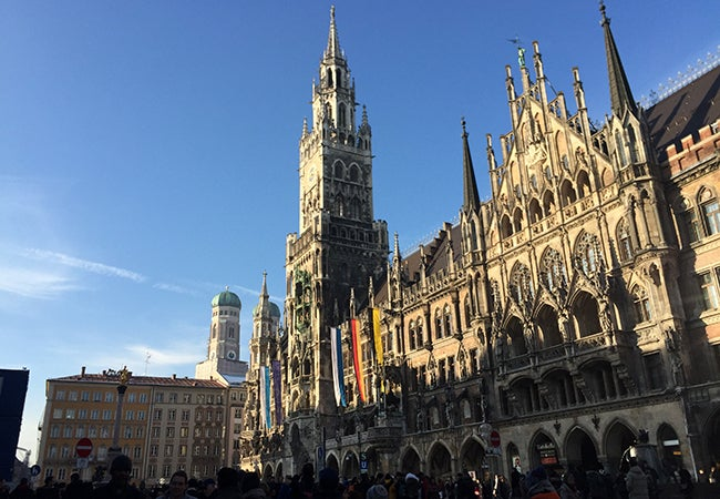 Flags drape across the front of a grandiose stone building in Munich.