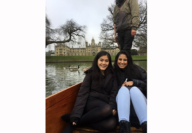 Business student Natasha Lim poses with a friend on a boat in front of a massive stone building in Cambridge.