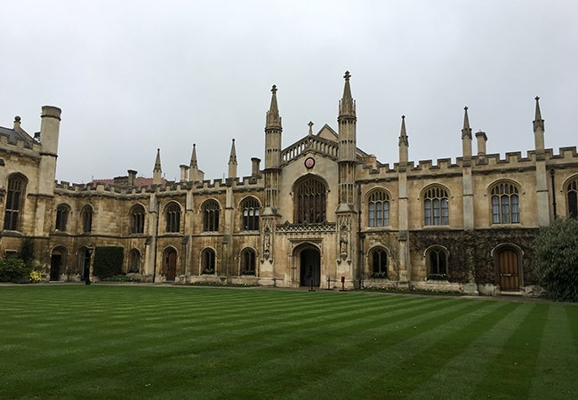 A very old stone building on the Cambridge campus sits on a perfectly manicured lawn.