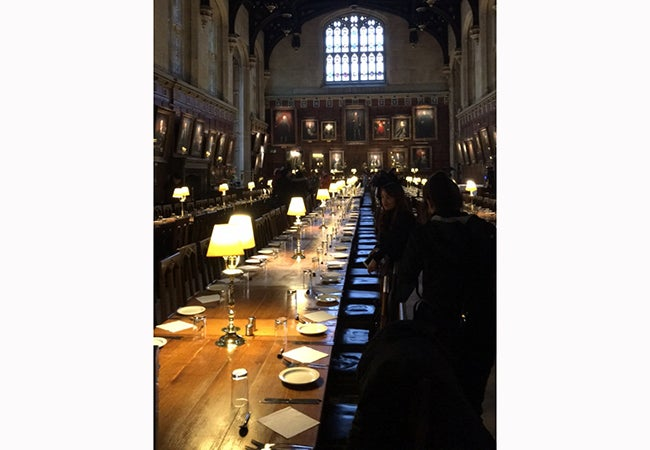 A large dining hall at Oxford includes portraits of university leaders and desk lamps illuminating long wooden tables.