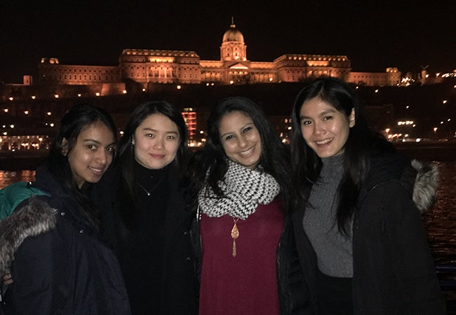Undergraduate business student Natasha Lim links arms with friends during a nighttime river cruise in Budapest.