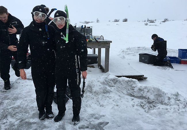 Two business students dressed in black wetsuits and snorkeling gear pose in front of an icy opening in the water on a frigid day.