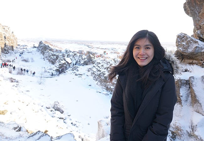 Undergraduate business student Natasha Lim smiles while standing in a snowy landscape with fellow hikers in the background.