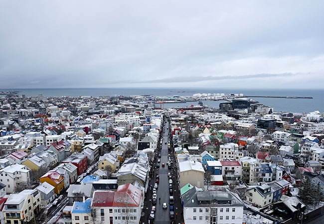 An aerial view of Reykjavik, Iceland shows a smattering of snow amongst colorful rooftops and brightly-colored homes.