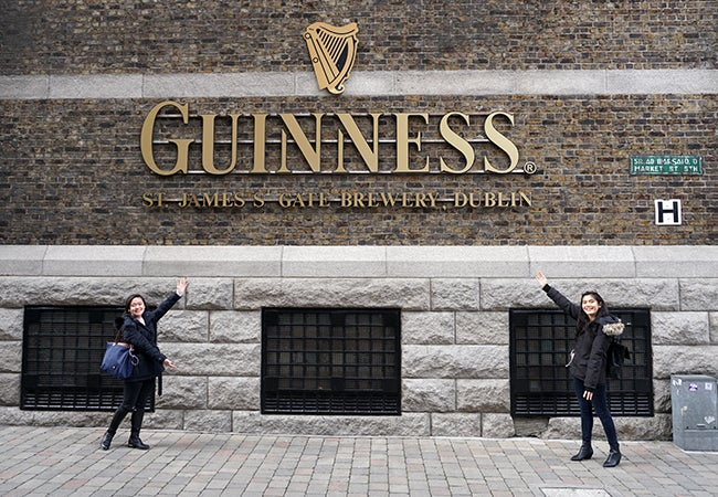 "Undergraduate business student Natasha Lim and her friend point to a large golden sign that says ""Guiness"" on the brick exterior of a brewery.."
