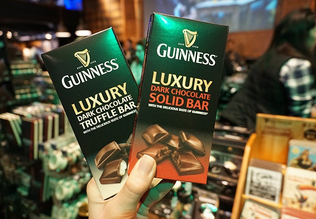 A hand holds up two Guiness dark chocolate bars encased in green packaging.