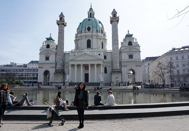 Undergraduate business student Natasha Lim stands in front of an ornately-decorated white stone building in Vienna.