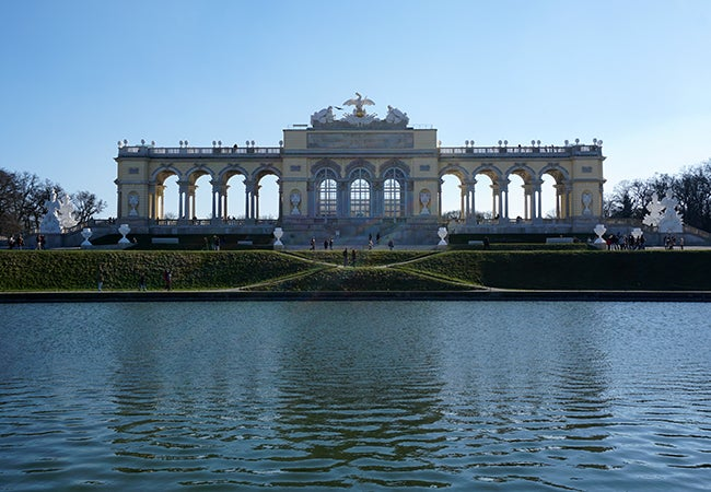 Visitors mill around the large fountain and spectacular gates in front of Schönbrunn Palace in Vienna.