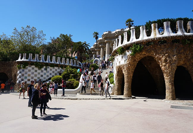 Visitors descend a sunny staircase lined with colorful tiles at Park Güell in Barcelona.
