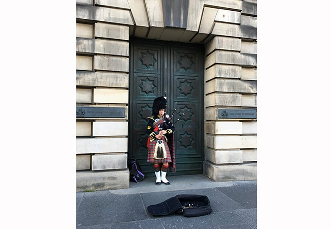 A bagpipe player wearing traditional dress stands in a doorway to play to passersby behind a suitcase open to collect coins.