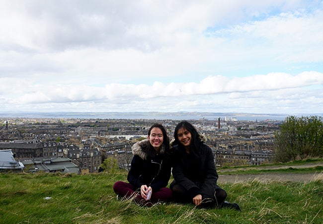 Business students sit in a grassy field in Scotland that overlooks the city of Edinburgh during a study abroad trip.