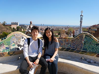 Undergraduate business student Natasha Lim poses with a friend on a colorful mosaic park bench in Barcelona.