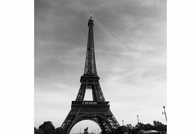 A black-and-white photograph shows the Eiffel Tower on a clear day.