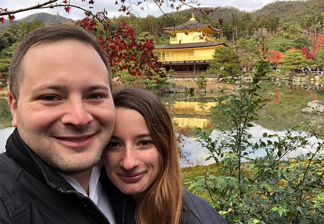 Part-time MBA student Ryan and his girlfriend stand in a garden in Japan with a vivid red tree and a golden structure in the background.