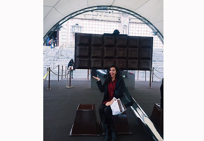 Business student Alexandra Grieco points to a huge chocolate bar on display behind her in Perugia at the famous Euro-Chocolate Festival.